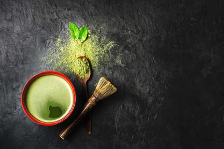 A bowl of matcha tea with scattered powder on a dark background with copy space. Top view.