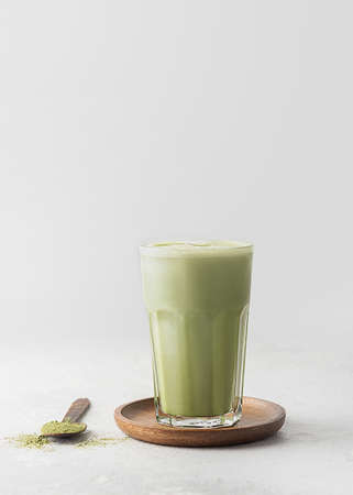 A glass of matcha latte tea on gray concrete with a copy space. Reklamní fotografie