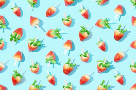 Juicy strawberries on a stick on a bright blue background with sharp shadows. Reklamní fotografie