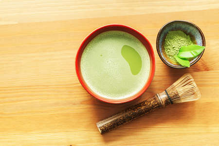 A bowl of matcha tea on a wooden table with a whisk and powder with copy space. 免版税图像