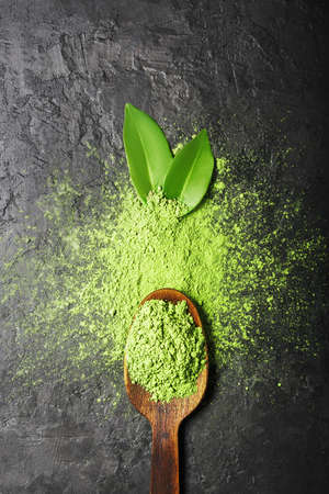 Matcha tea powder on dark background with spoon and leaves with copy space.