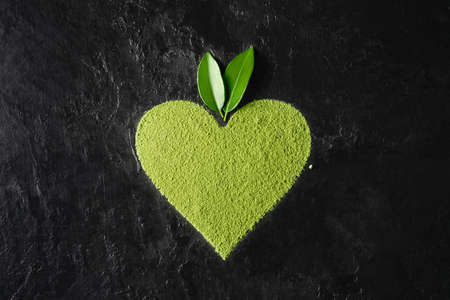 Powder matcha tea in the shape heart on a dark background. Top view.
