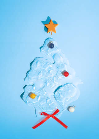 Christmas tree in the shape of melting ice on a blue background. Top view.