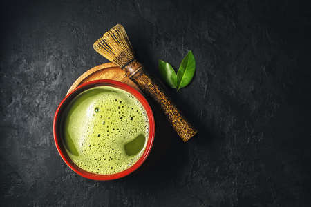 Bowl of matcha tea with whisk on dark background with copy space. Top view. 免版税图像