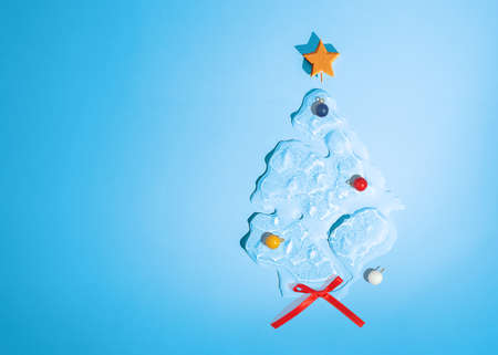 Christmas tree in the shape of melting ice on blue background with copy space. Top view.