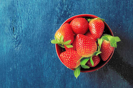 A bowl of juicy strawberries on a dark blue background with copy space.