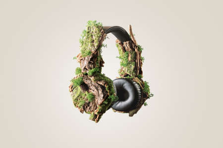 The creative concept of slowing down.Headphones overgrown with wood bark and moss on a beige background. 免版税图像