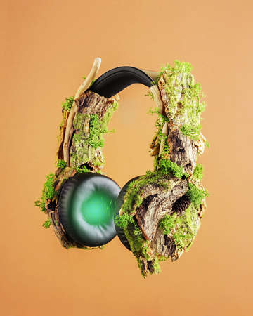 The creative concept of slowing down.Headphones encrusted with wooden bark and moss on an orange background.