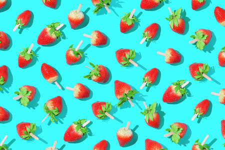 Juicy strawberries on a stick on a bright blue background with sharp shadows. 免版税图像