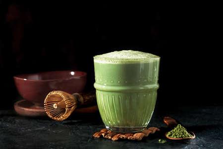 A glass of matcha tea on a dark concrete background. 免版税图像