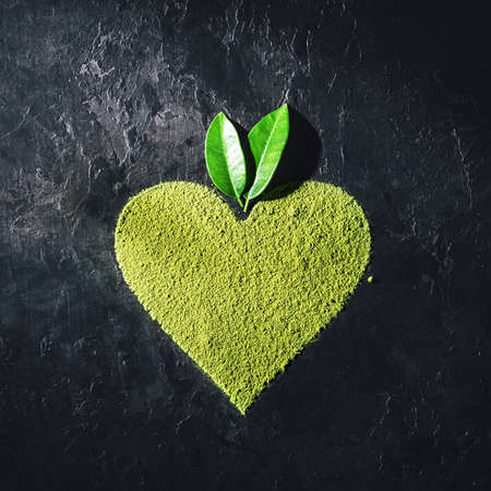 Green natural heart shaped powder with leaves on a dark concrete background.