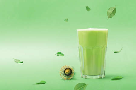 Glass of ice match latte on green background with copy space.