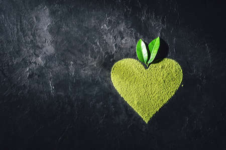 Green natural heart shaped powder with leaves on a dark concrete background with a copy space. 免版税图像