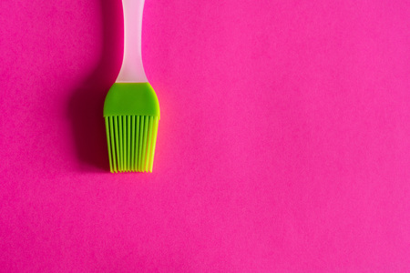 green silicone brush with white handle on pink background top view Фото со стока