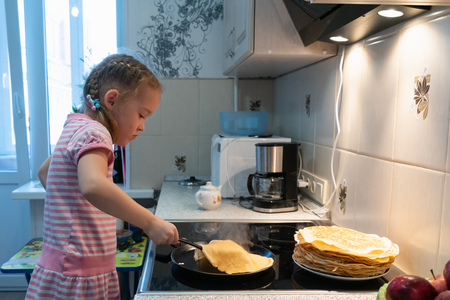 little girl in pink dress frying pancakes on electric stove at home Standard-Bild - 121637071