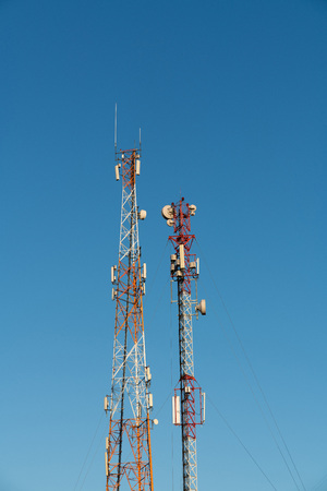 metal red-white radio Tower with equipment against the blue sky