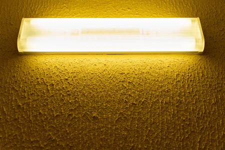 light fluorescent lamp with white light on the wall with yellow surface Фото со стока