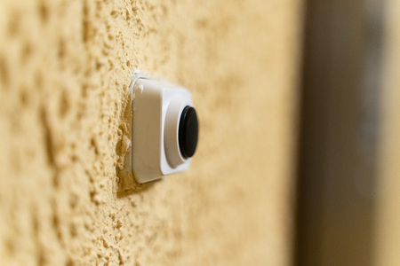 black doorbell button in white case on yellow wall with embossed texture close-up