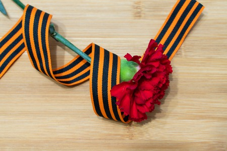 carnation and St. George ribbon on wooden background as victory day greeting cards