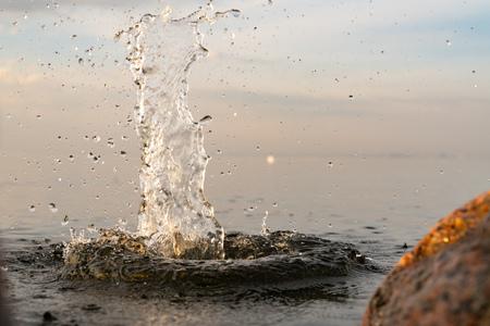 beautiful splash of water in the sea at sunset. natural desktop background