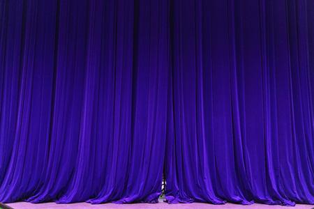 gesloten blauwe gordijn achtergrond spotlight lichtstraal verlicht. Theatrale gordijnen. Behangontwerp