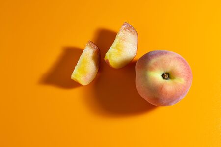juicy fresh ripe peach on orange matte background. fruits and healthy food Stockfoto