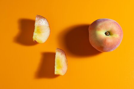 juicy fresh ripe peach on orange matte background. fruits and healthy food Foto de archivo