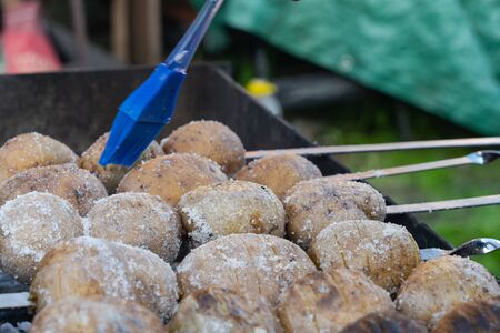potatoes baked on the coals on the grill with a nice brown crust oiled blue tassel . food preparation and cooking