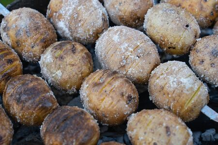 baked potatoes on the coals on the grill with a Golden crust. food preparation and cooking