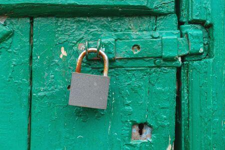 hinged old metal lock on old green wooden door Reklamní fotografie