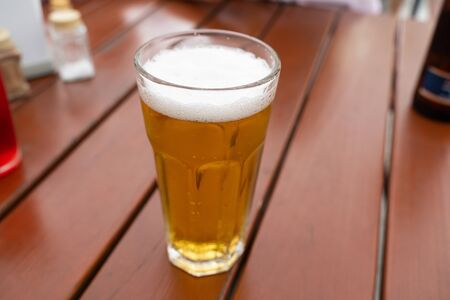 a glass of light wheat beer on a wooden table close-up. template for Wallpaper design or cafe menu