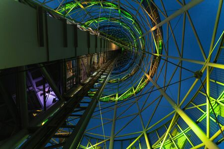 abstract metal design of the tower with green neon lights at night, the view from below Stock fotó