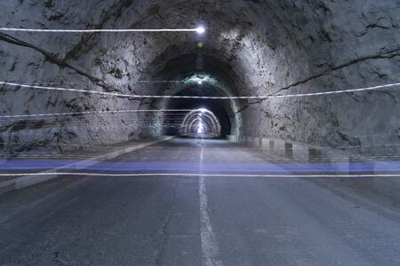 mountain tunnel with artificial light and the rocky walls of the front view. asphalt road