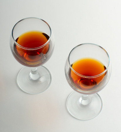 two wine glasses from brandy on a gray non-uniform background Stock Photo