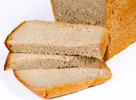 cutoff: the loaf of rye bread with the cut-off pieces lies on a light surface