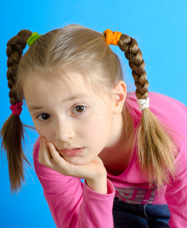 affability: the girl of 9 years with two braids poses in studio. The photo on a blue background Stock Photo