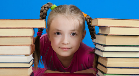 the girl of 9 years sits near a pile of books and smiles. The photo on a blue background photo