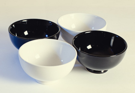 whitern: four bowls: two white and two black stand on a light surface. Stock Photo