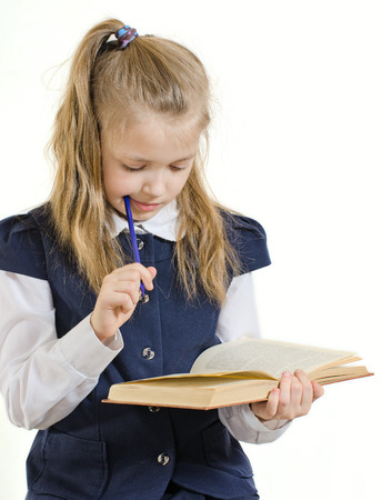attentiveness: the girl of 9 years in a school uniform reads the book. Holds a pen in the right hand
