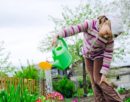 inclination: The girl of nine years in a warm pullover and brown jeans waters color in a garden from a green watering can Stock Photo