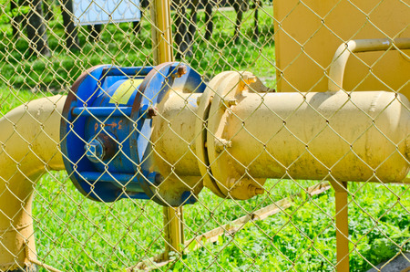flange: part of the equipment of gas station of yellow color. at the left the flange painted blue color. In total behind an iron grid.
