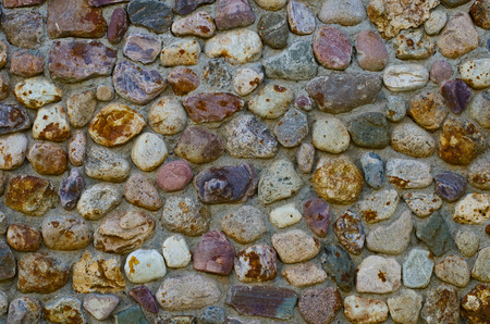 the heterogeneity: The wall fragment put from a natural stone Stock Photo