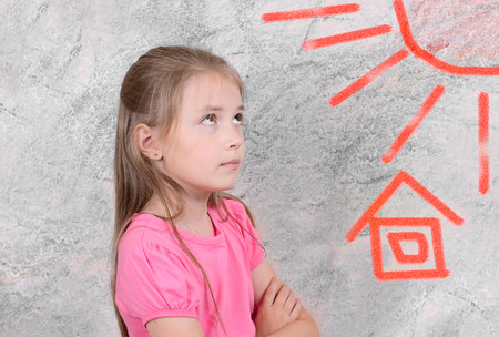 the girl of 9 years looks at the red sun and the house. A background - gray texture,