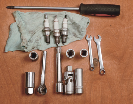 carburetor: tools for car repairs and a spark plug on a dark wooden background