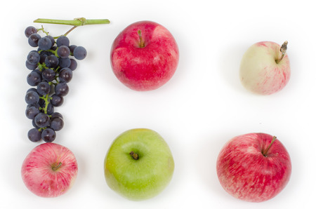 certain: cluster of grapes are laid out on a light surface in a certain order