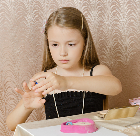 hairpin: the girl of nine years puts on a ring a finger Stock Photo