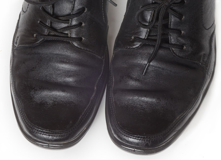outsole: two black mens Shoe treated with Shoe- Polish stand on a light surface
