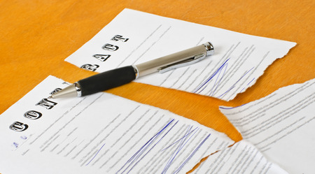 broken contract: broken contract with a pen lying on a wooden surface. Stock Photo