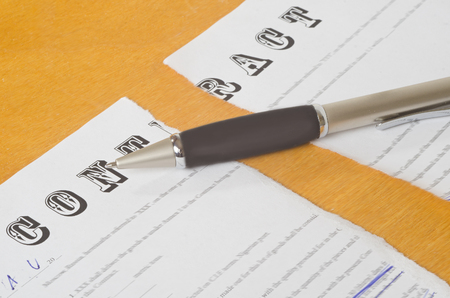 criterion: broken contract with a pen lying on a wooden surface. Stock Photo