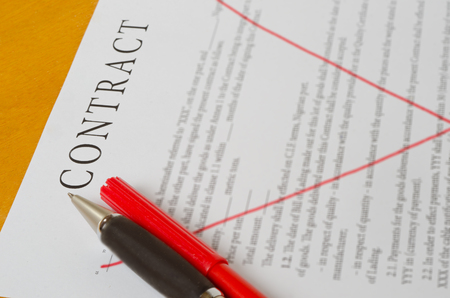 crossed the red lines of the contract with a pen lying on a wooden surface.